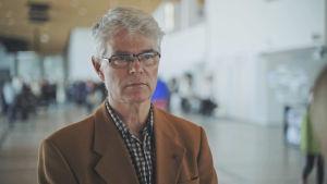 Jan Löfstedt intervjuas i biblioteket Oodi. Han har en brun kavaj och rutig skjorta på sig.