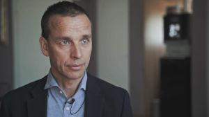 Stressläkare Markus Sundblom intervjuas på Eira sjukhus. Han är klädd i mörk kavaj och blå skjorta.