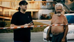 kaksi miestä seisoo kadulla jonkinlaisen poliisinauhan takana.