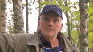 Matts Cygnell, en man med blå skärmmössa, tittar fundersamt mellan trädstammar.