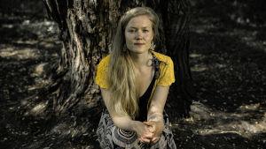 Viivi Sihvonen istuu jykevän puunrungon edessä.
