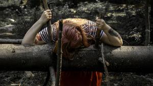 Nainen polvillaan, pää vasten kaatunutta puunrunkoa. Naisen kädet pitävät kiinni terävän näköisistä oksista, jotka osoittavat taivasta kohden.