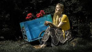 Viivi Sihvonen istuu nurmikolla kukkaistutuksen vieressä. Silmät ovat kiinni ja aurinko osuu hänen kasvoilleen.