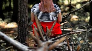 Nainen istuu kaatuneen puun päällä selkä kameraan päin. Puusta törröttää teräviä oksia.