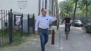 Invånaren Bert Nap vinkar åt en granne utanför sitt hus i De Wallen i Amsterdam.