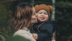 Äiti pussaa poikaansa poskelle.