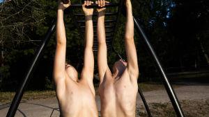 kaksi miestä roikkuu kiipeilytelineessä