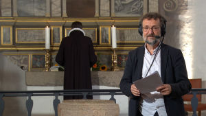 TV-regissören Flemming Stentoft står med hörlurar på huvudet framför altare i dansk kyrka.