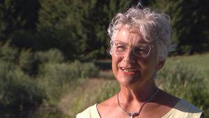 Prästen Elisabeth Lidell i sommarlandskap.