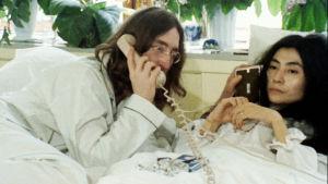 John Lennon ja Yoko Ono valkoisissa yöpuvuissa sängyssä. Kuva dokumenttielokuvasta John & Yoko: Above Us Only Sky.