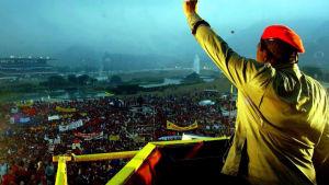Presidentti Hugo Chávez puhuu suurelle ihmisjoukolle. Chávez seisoo selkä kameraan päin punainen baretti päässä. Hän on puristanut toisen kätensä nyrkkiin ja kohottanut sen ilmaan.