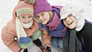 Lapset poseeraavat jäällä