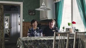 Ett äldre bar sitter vid ett köksbord i ett grönt och dunkelt kök. Båda ler.