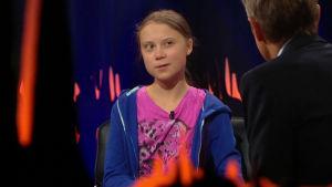Greta Thunberg intervjuas av Fredrik Skavlan. I mitten av bilden syns Thunberg och i högermiljö Skavlan.