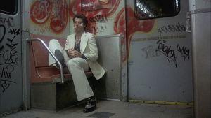 Tony (John Travolta) istuu masentuneena aamuisessa metrovaunussa elokuvassa Saturday Night Fever - lauantai-illan huumaa