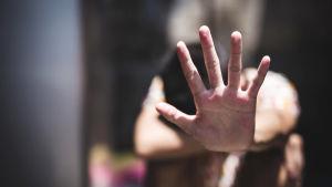 Kvinna håller ut handen som för att säga stopp.