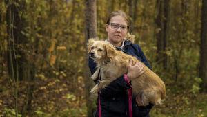 Oululainen Miia Seppälä pitää koiraansa sylissä