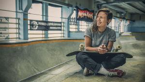 Nainen istuu skeittilaudallaan.