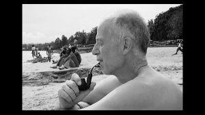 Thomas Elfgren sitter på en strand i Rwanda och röker pipa.