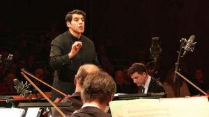 Kapellimestari johtamassa orkesteria.
