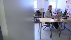 Nainen istuu tietokoneen ääressä.