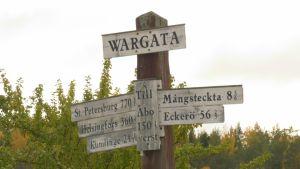Skylt på Vårdö, på skylten står avstånd till olika orter, till exempel Helsingfors, Kumlinge och S:t Petersburg.