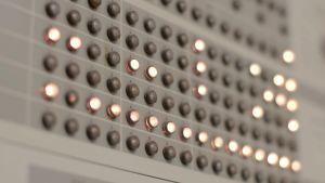 IBM 1800 -tietokoneen käyttöpaneeli. Valoja syttyy ja sammuu.
