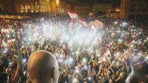 En dj blickar över publikhav under demonstrationerna i Beirut, Libanon. Publiken har flaggor i händerna och telefonernas ljus bildar ett ljushav bland publiken.