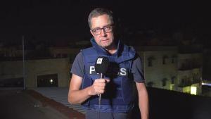 En reporter med Yle-mikrofon står med en skottsäker väst på ett tak. Det är kväll.