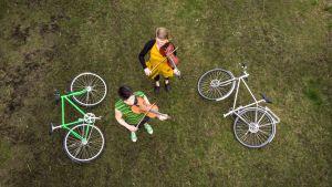 Kuvassa Duo Emilia Lajunen & Suvi Oskala. Kuvattu ylhäältä, Duolla käsissä viulu ja vierellä polkupyörät kaatuneina maassa