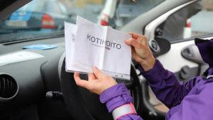 Kotihoitaja Raija Riikonen esittelee pysäköintilappua. LÄHIKUVA