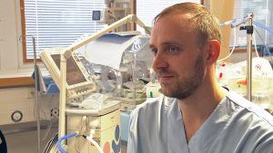 En manlig barnläkare sitter i ett rum på sjukhuset.