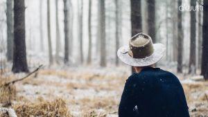 Mies selin kameraan, katsoo lumiseen metsään.