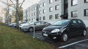 En rad bilar parkerade bredvid varandra vid ett husbolag.