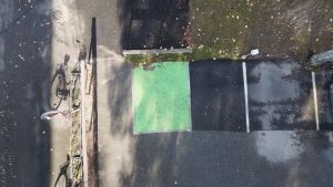 Ett grönt område målat på svart asfalt för elbilar som ska laddas.