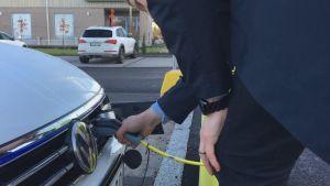 En man sätter sladden in i en elbil som ska laddas.