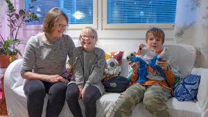 lapset ja hoitaja istuvat sohvalla