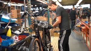 Cykelmontör Patrik Lindström bygger ihop en elcykel.