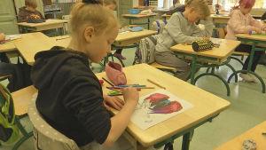 En flicka som tecknar vid sin pulpet.