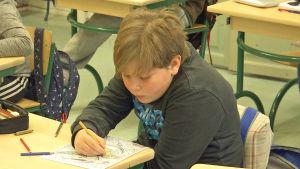 En pojke som tecknar vid sin pulpet.