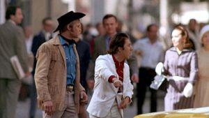 """""""I'm walking here!"""" """"Minä kävelen tässä!"""" Ratso Rizzo (Dustin Hoffman) huutaa vihaisena taksiautoilijalle newyorkilaisella suojatiellä elokuvassa Keskiyön cowboy. Joe Buck (Jon Voight) katsoo vieressä."""