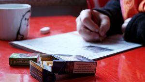 Pöydällä tupakka-aski, kahvikuppi ja ristikoita.