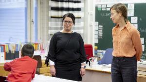 Li Andersson keskustelee opettajan ja oppilaan kanssa Varissuon koulun luokassa.