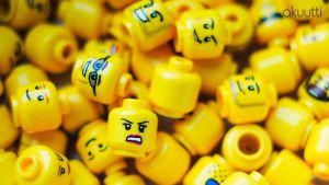 Lego-hahmojen päitä, joissa erilaisia ilmeitä.