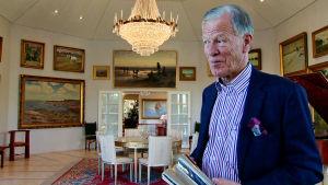 Anders Wiklöf står framför sina tavlor.