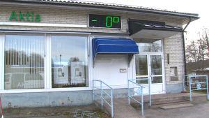 Aktia Banks kontor i Nagu, en vit tegelbyggnad med en blå markis utanför.