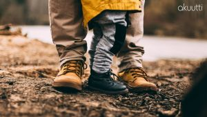 Aikuisen ja lapsen jalat syksyisessä metsässä.