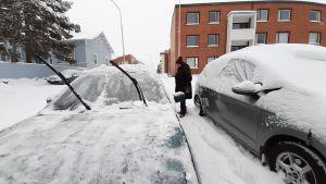 Nainen puhdistaa autoa lumesta.