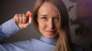 Marjut Mäntymaa pitelee kädessään DNA-näytepulloa