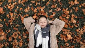 Wilhelmiina Vihreälehto makaa maassa syksyn lehtien keskellä, silmät kiinni, hymyillen.